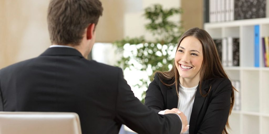 A woman dressed in business attire smiles as she shakes the hand of a man wearing a suit.